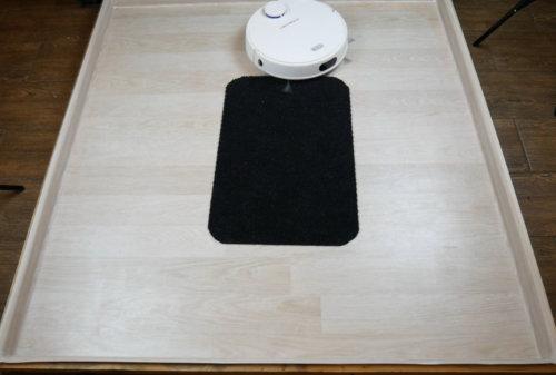 Робот-пылесос и черный коврик